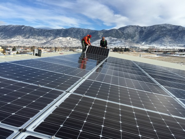 Our installers laying down the last solar module in front of the mountainous backdrop of Butte, MT