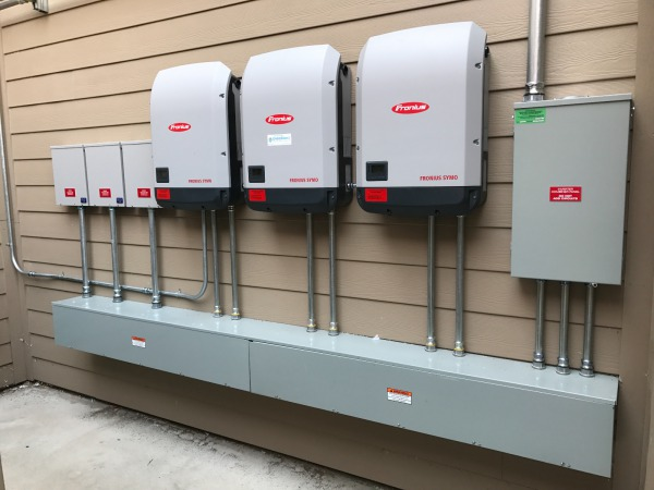 Three Fronius Symo 15 kW inverters, mounted outside on a well-protected wall